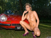 Natalie Forrest naked next to a classic red ferrari